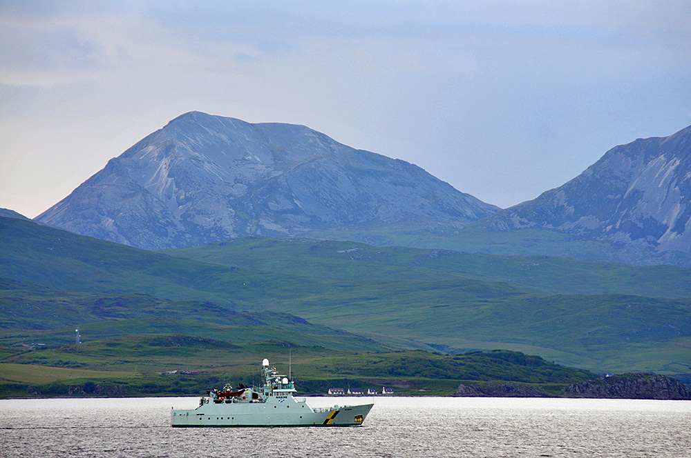 Picture of a marine protection vessel passing an island with high mountains