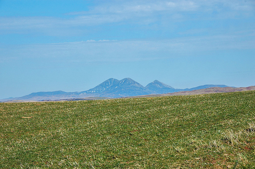Picture of three mountains in the distance behind some grassland