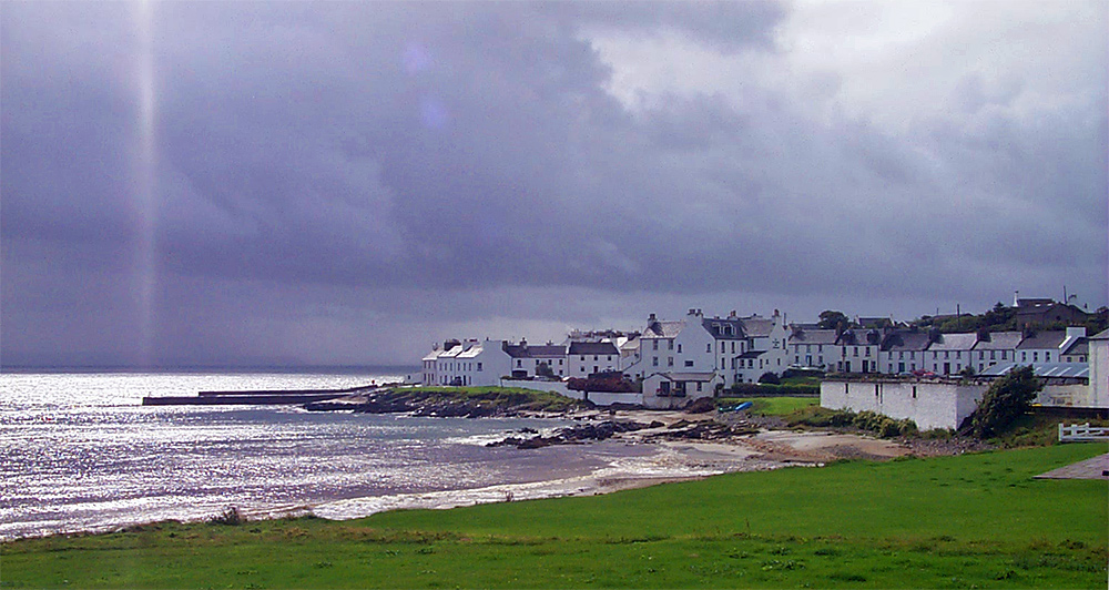 Picture of a coastal village under black clouds of a shower, sun breaking through