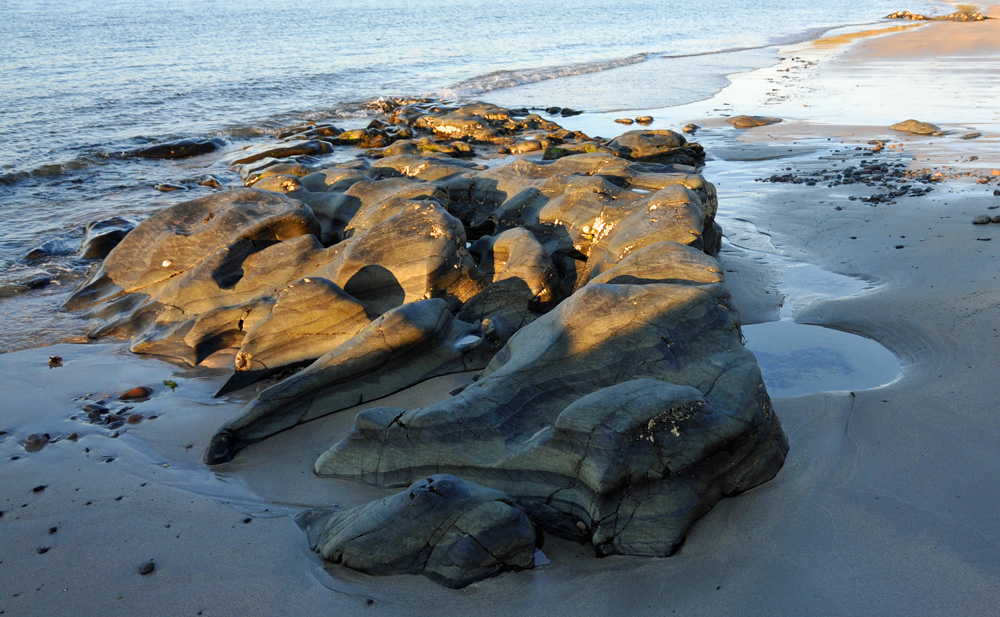 Picture of rocks on a beach in the mild evening light