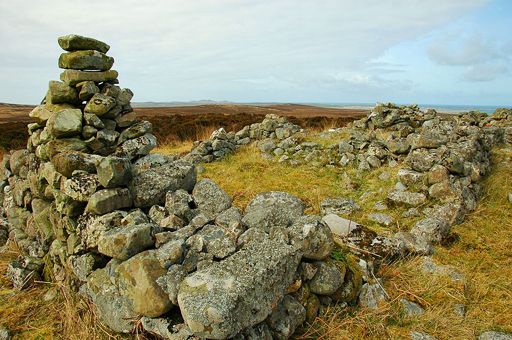 Picture of the ruins of a former croft in hills above a coast