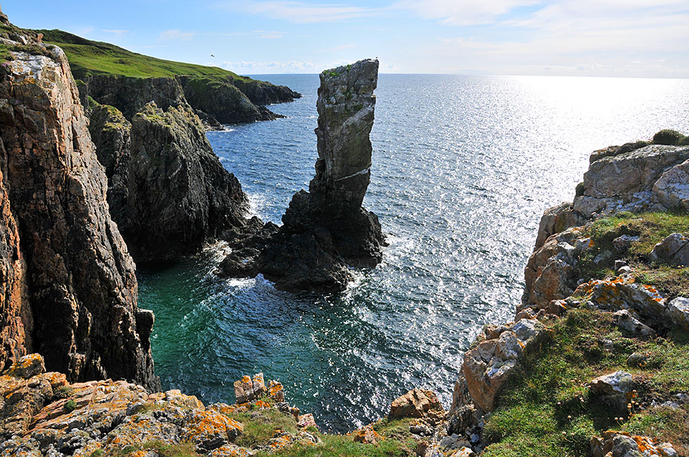 Picture of a view of a sea stack from the cliffs next to it