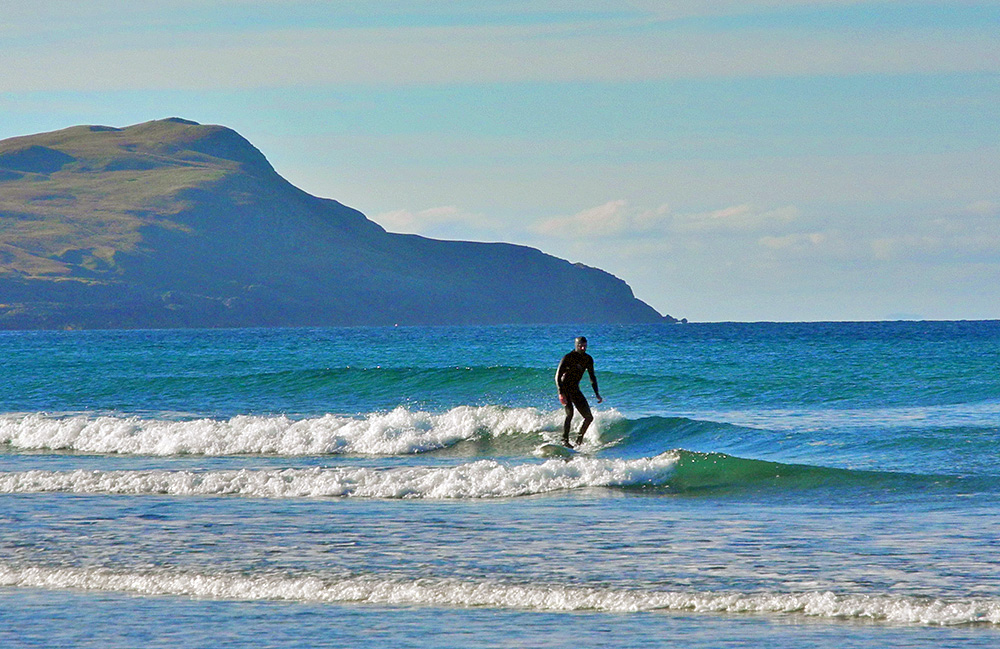 Picture of a surfer on small waves on a sunny autumn day