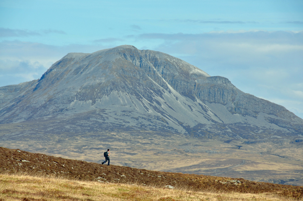 Picture of a walker in front of a scree covered mountain