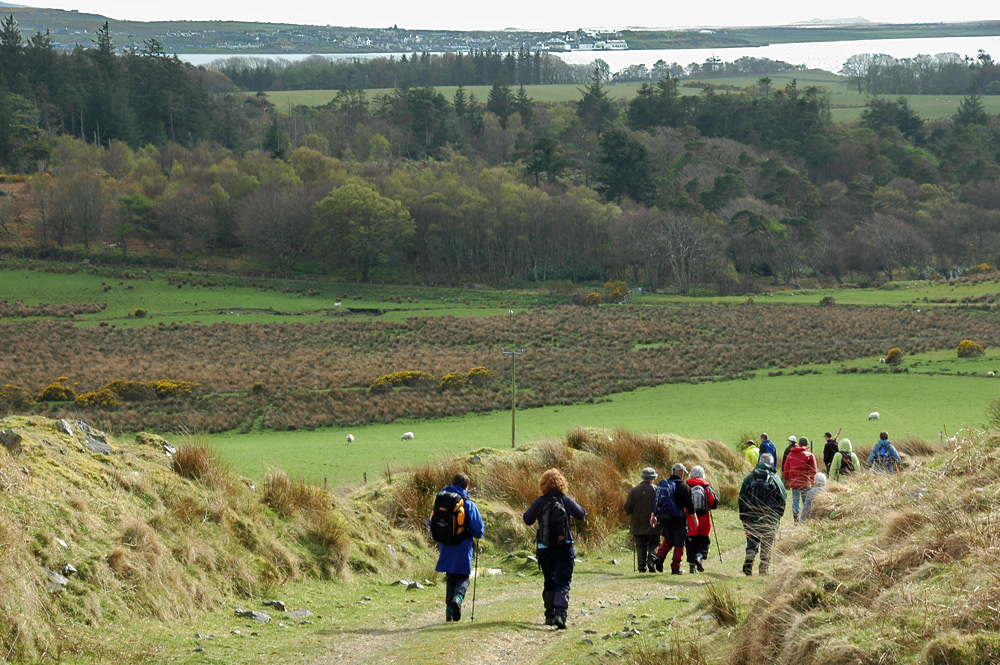 Picture of a group of walkers on a track, a sea loch and a village in the distance