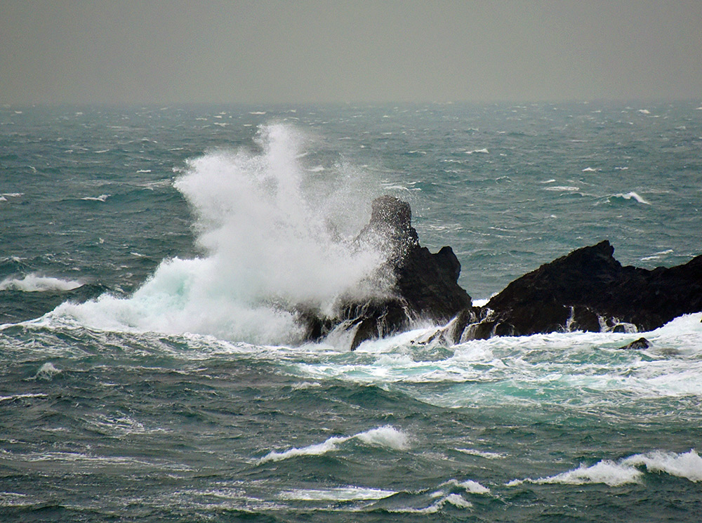 Picture of a wave breaking over rocks sending spray high in the air