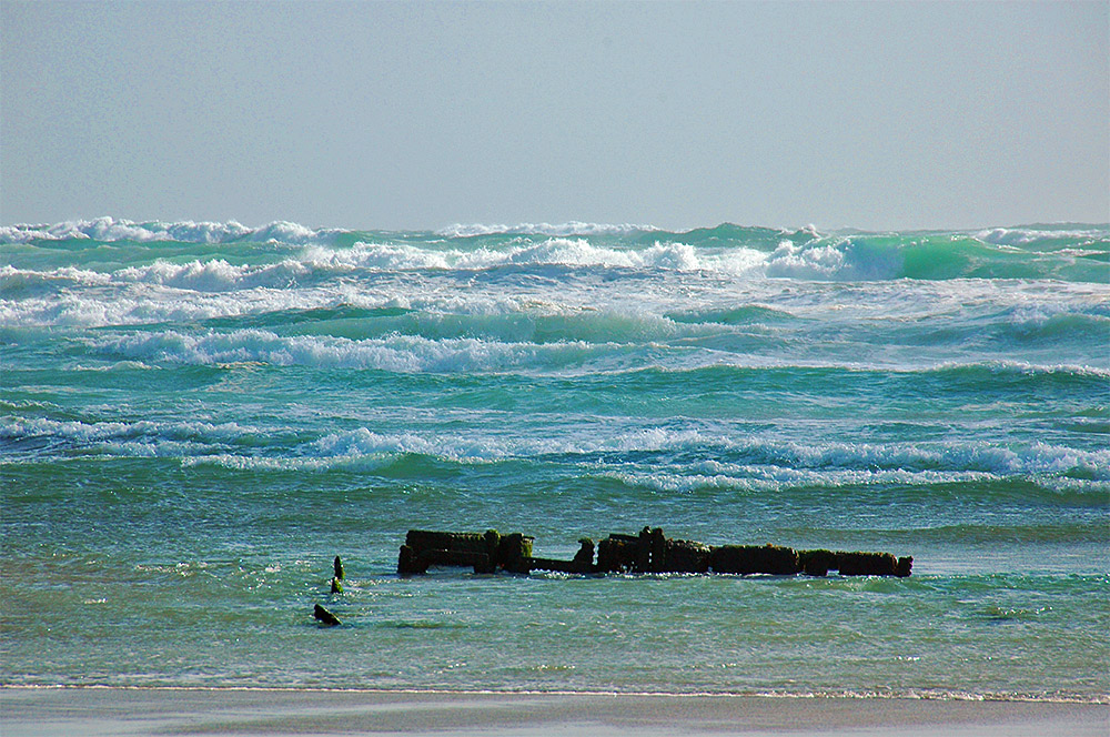 Picture of waves rolling on to a beach with the remains of a shipwreck