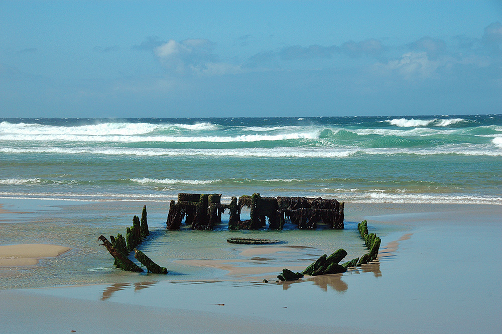 Picture of an old wreck on a beach, waves rolling in in the background