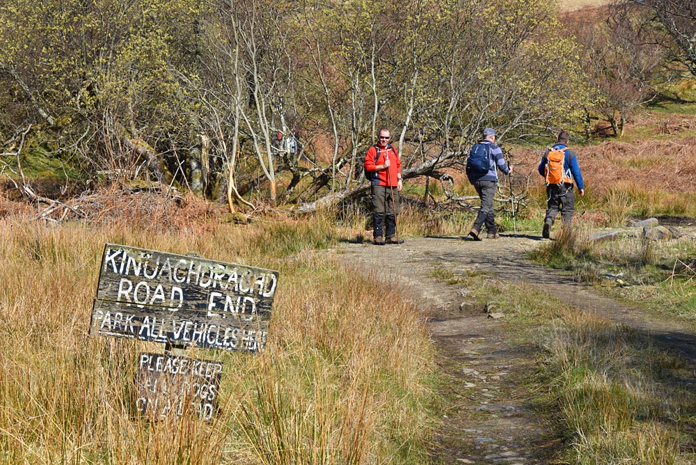 Picture of walkers at a track near to a sign proclaiming the end of the road