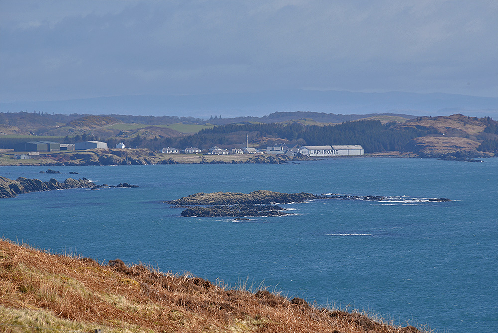 Picture of a coastal distillery seen across the sea