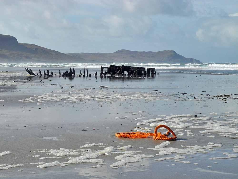 Picture of a wreck on a beach, next to it a piece of frayed rope