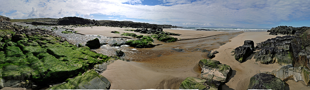 Panoramic picture of a small river running on to and over a beach into the sea