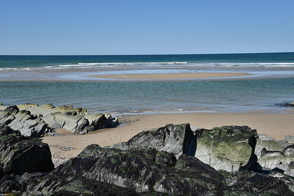 Picture of a small sandbank off a beach with rocky sections