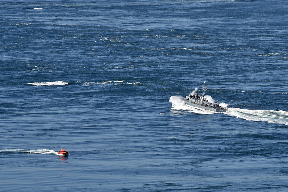 Picture of a German Navy ship and a Scottish RIB at a whirlpool