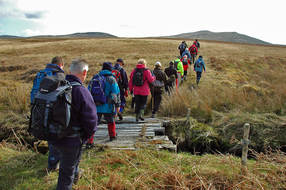 Picture of a group of walkers crossing a small bridge on their way to some hills
