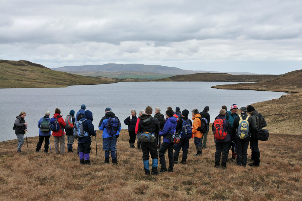 Picture of a group of walkers above a loch on a cloudy day