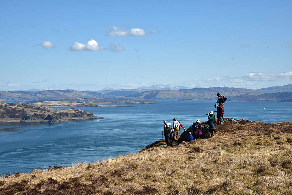 Picture of a group of walkers high above a gulf between two islands, the mainland also visible in the background
