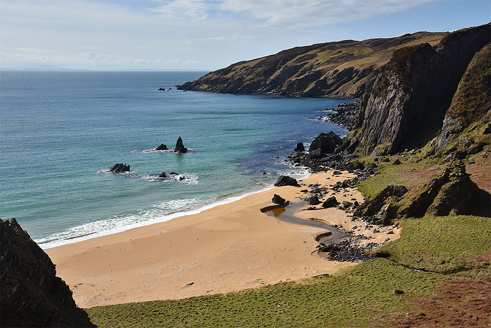 Picture of a small sandy beach in a cove in beautiful sunshine