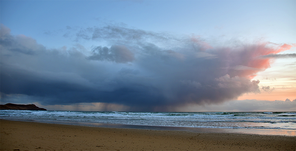 Picture of a rain shower passing over a bay in the last light just after sunset