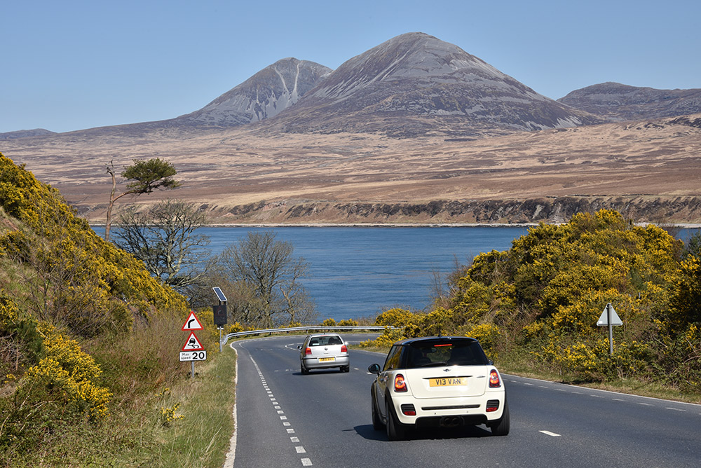 Picture of a steep road leading to a sound between two islands, two mountains on the other side of the sound