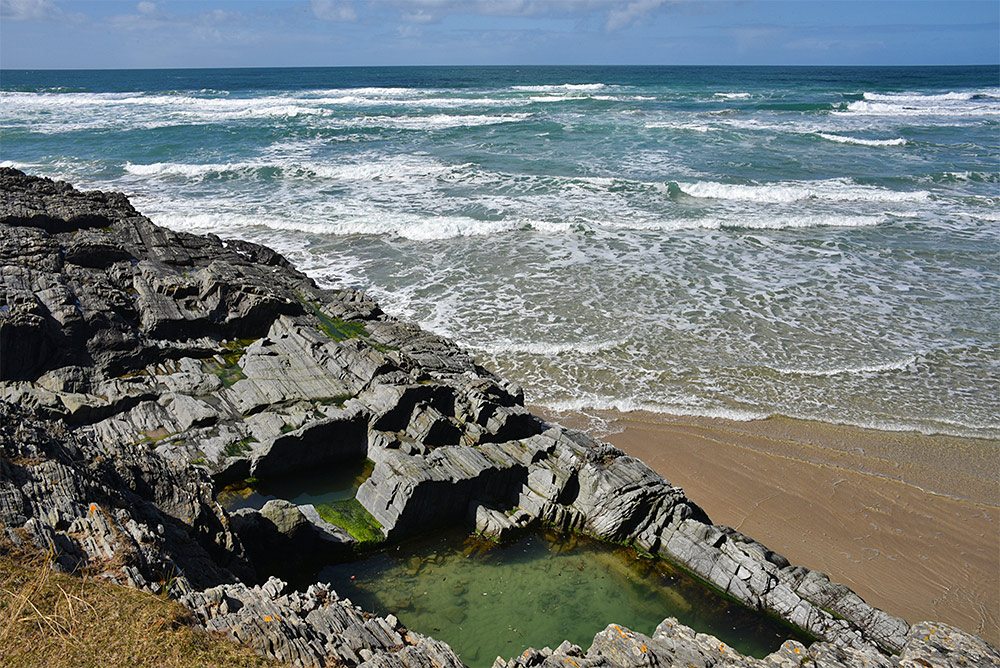 Picture of a rock pool above a sandy beach