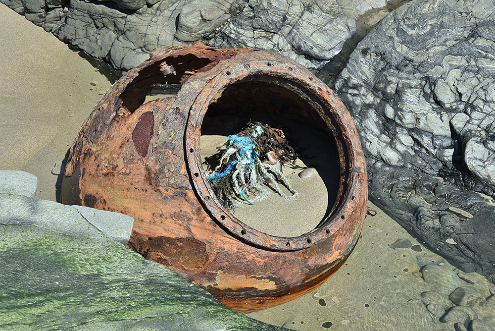 Picture of the remains of an old sea mine washed up on a beach and wedged between rocks