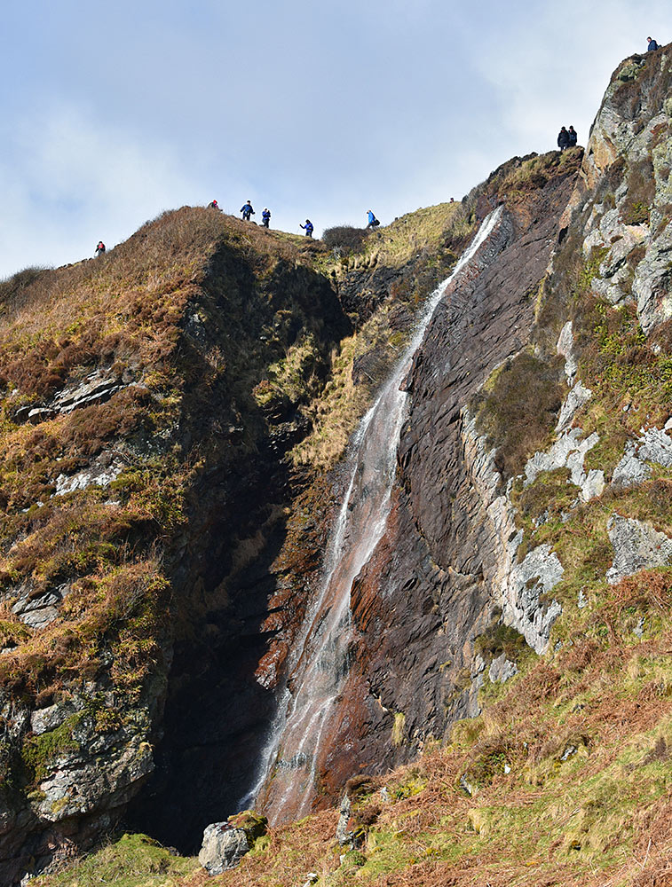Picture of a group of walkers standing above a tall waterfall