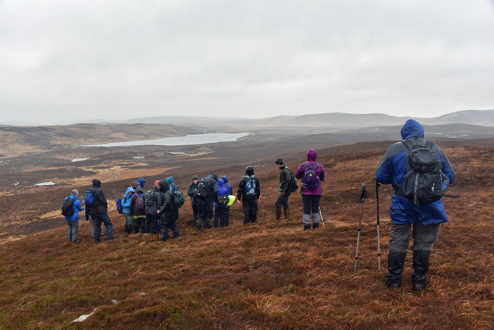 Picture of a group of walkers in the rain on a hillside above a loch (lake)