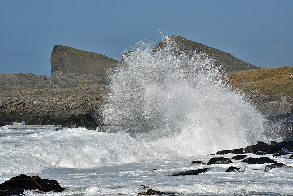 Picture of a big wave splash over rocks, distinctly shaped cliffs in the background