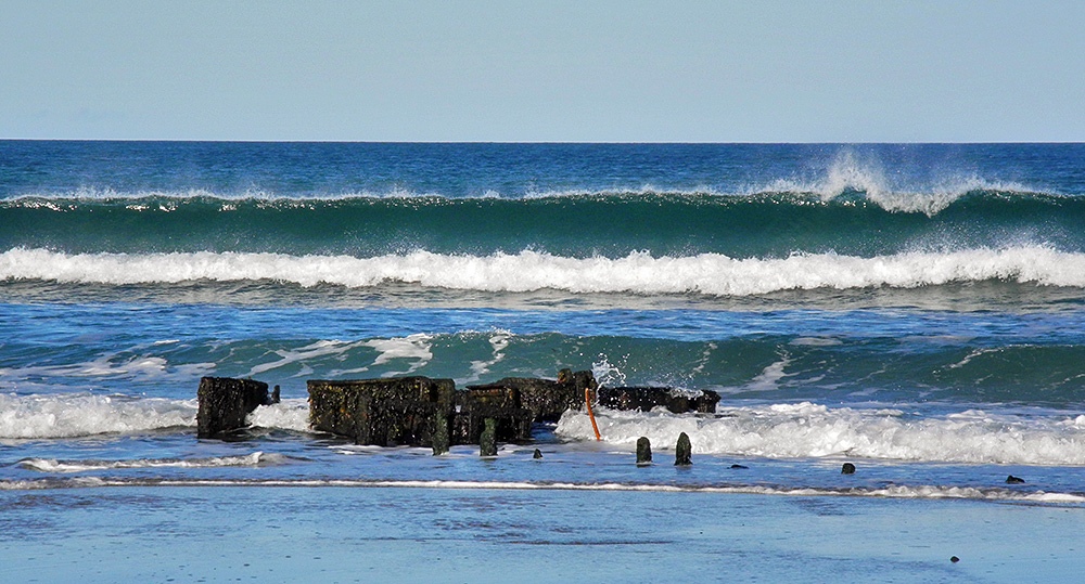 Picture of a wave starting to break behind a wreck on a beach