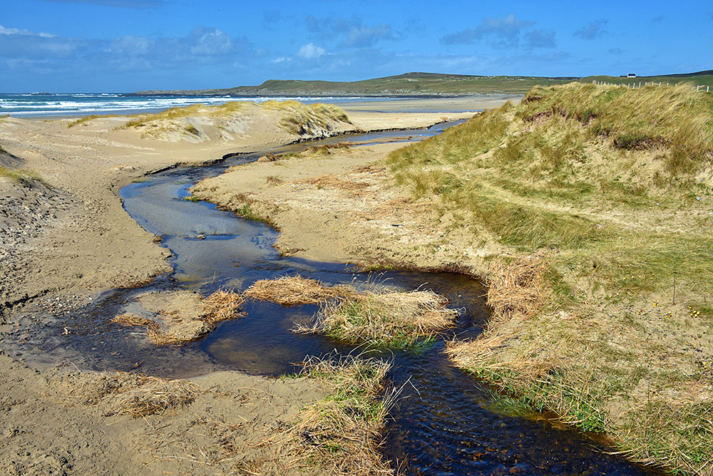 Picture of a burn (river) meandering across a beach towards the sea