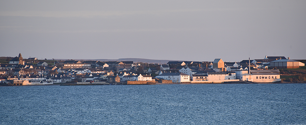 Picture of a coastal village in mild evening light seen across a sea loch