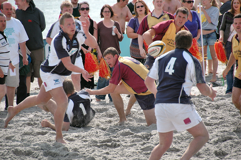 Picture of a player throwing a pass during a beach rugby game