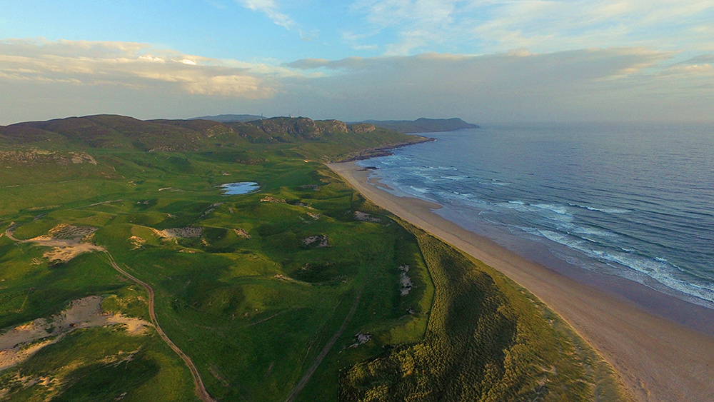 Aerial picture of coastal dunes and a beach in the mild evening light