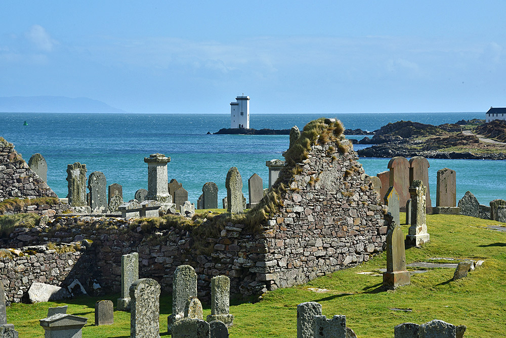 Picture of a view across a cemetery to the sea and a lighthouse