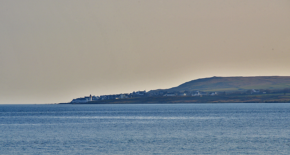 Picture of a view across a sea loch to a coastal village with a lighthouse on a calm evening