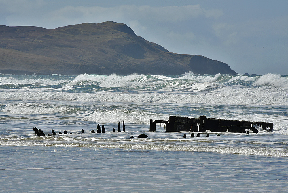 Picture of a bay with a big swell rolling in onto the beach, a wreck on the beach
