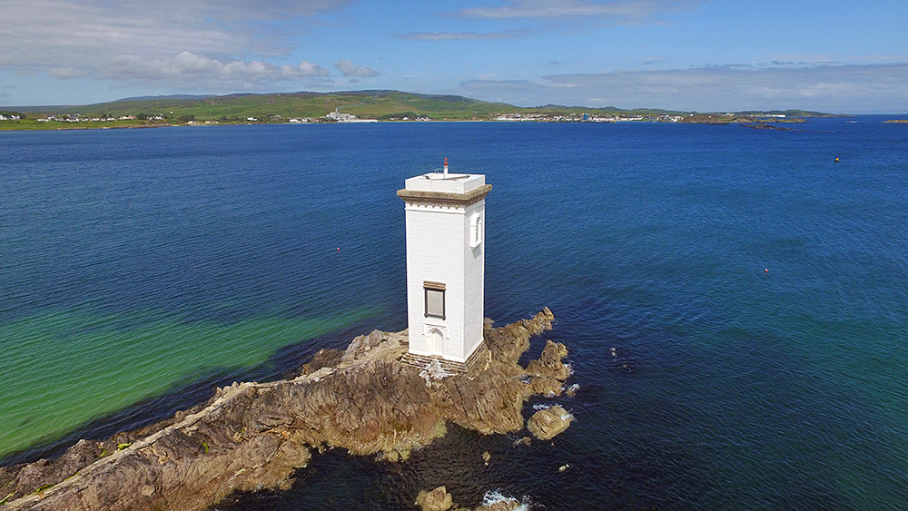 Picture of a square lighthouse with a harbour village in the distance