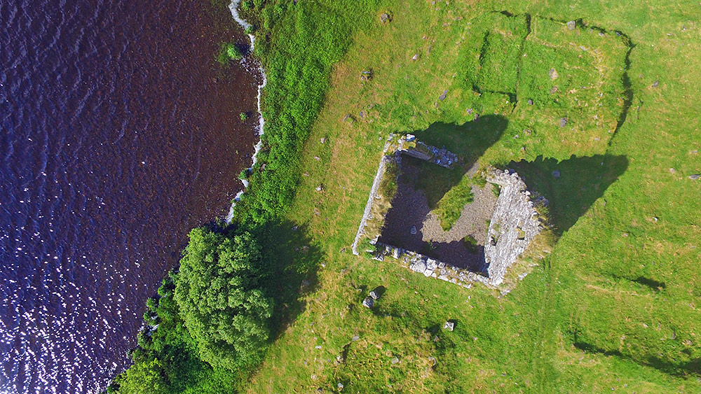 Picture of an old ruin of a house on the shore of a loch (lake) from the air