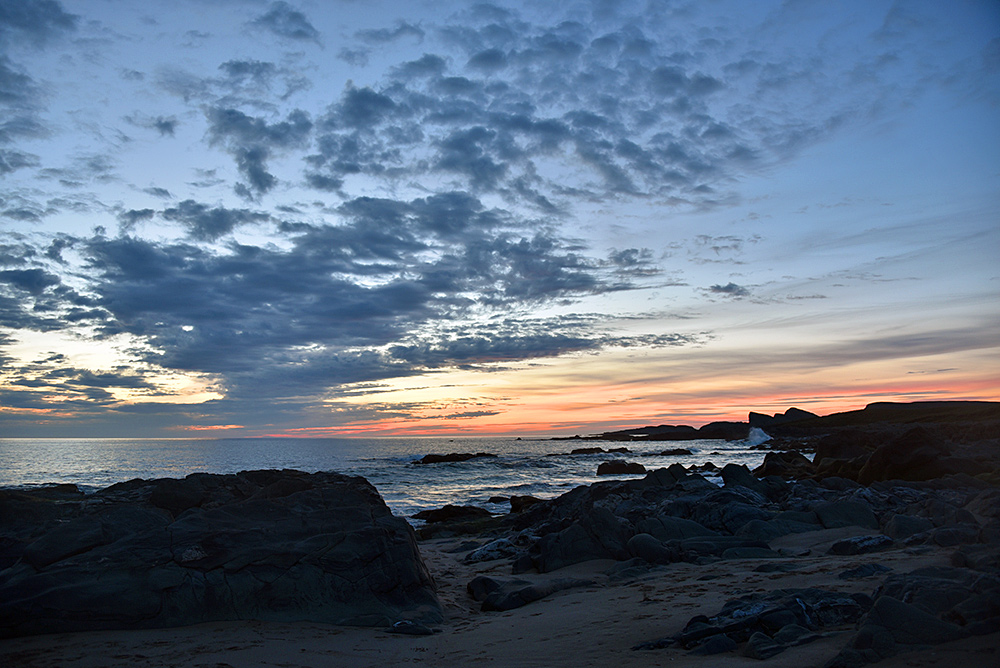 Picture of the gloaming on a coast with a mixture of beach and rocks