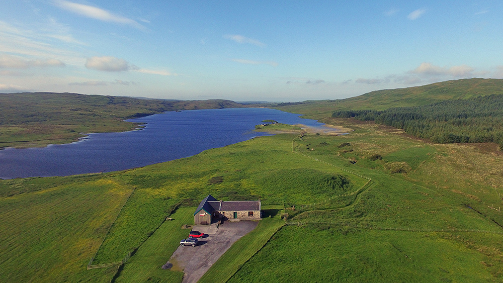Picture of a freshwater loch with two islands from the air, a visitor centre in the foreground