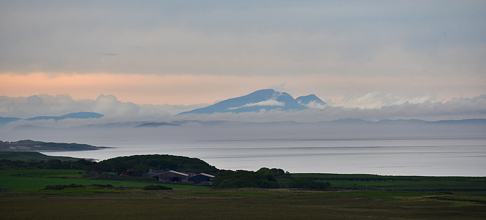 Picture of a cloud inversion around an island seen across the sea from another island