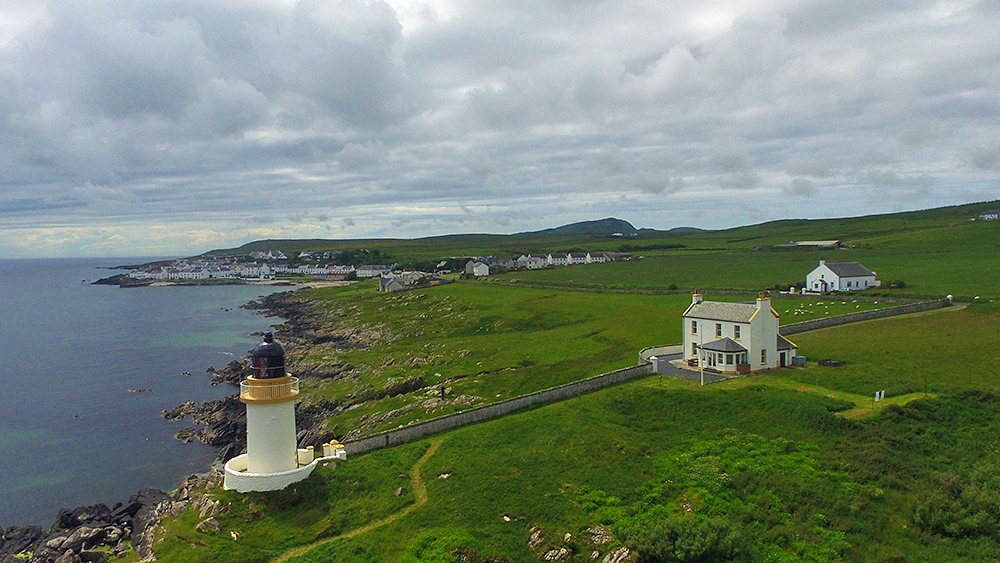 Picture of an aerial view of a lighthouse and an adjacent coastal village