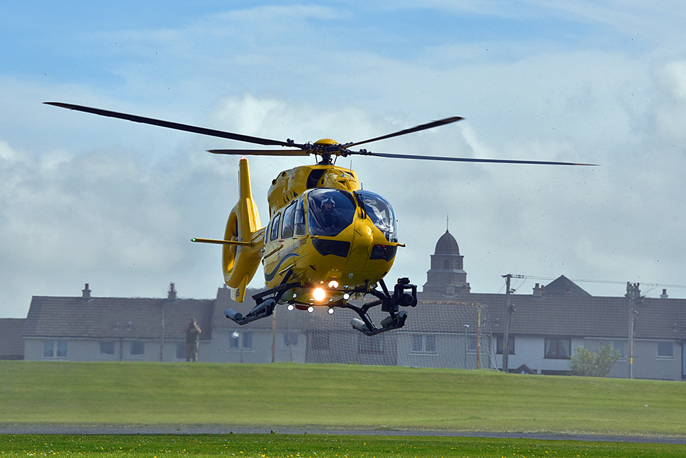 Picture of a yellow air ambulance helicopter taking off