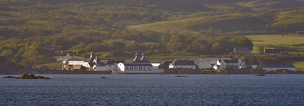 Picture of a coastal distillery in the evening light seen from a passing ferry