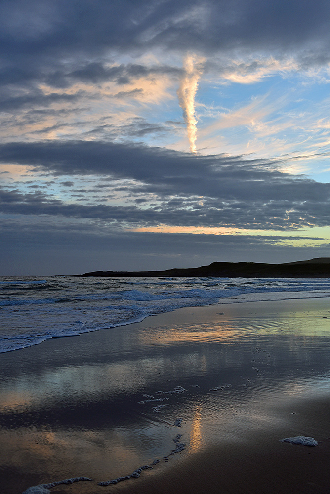 Picture of the gloaming watched on a beach on a partially cloudy evening
