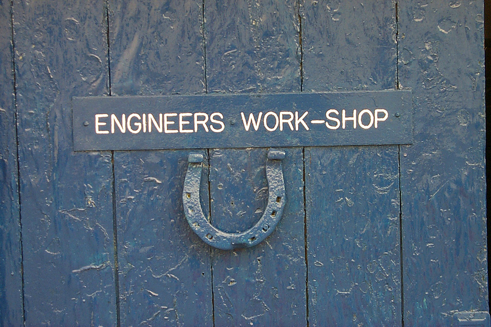 Picture of a sign on a wooden door reading Engineers Work-Shop, a horseshoe hanging below