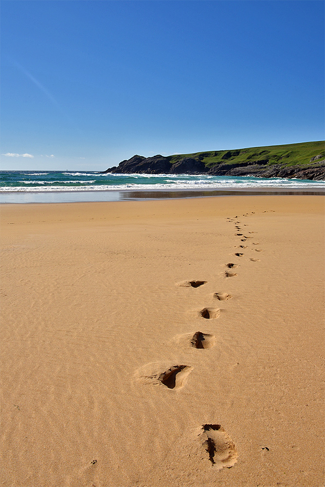 Picture of a single line of footsteps on a golden sandy beach under a blue sky