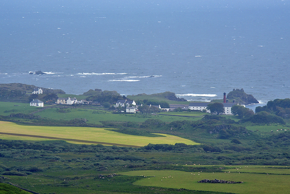 Picture of a coastal village and distillery with a castle ruin on the shore