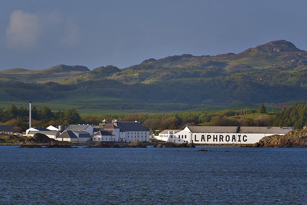 Picture of Laphroaig distillery in the evening light, seen from a passing ferry